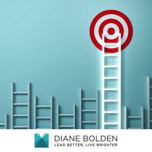 different size white ladders with the tallest ladder leading to a red and white bullseye target the represents living the dream