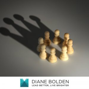 chess pieces with the shadow of a crown that implicates overcoming challenges in the shadow of a daunting task