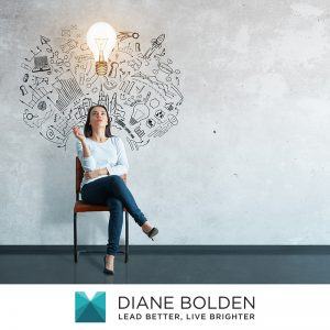 female sitting in a chair with a lightbulb lit up above her head and thinking about becoming a leader